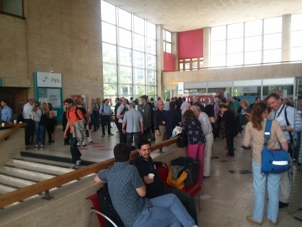 Conference attendees enjoying pains au chocolat, croissants, and coffee during a break.